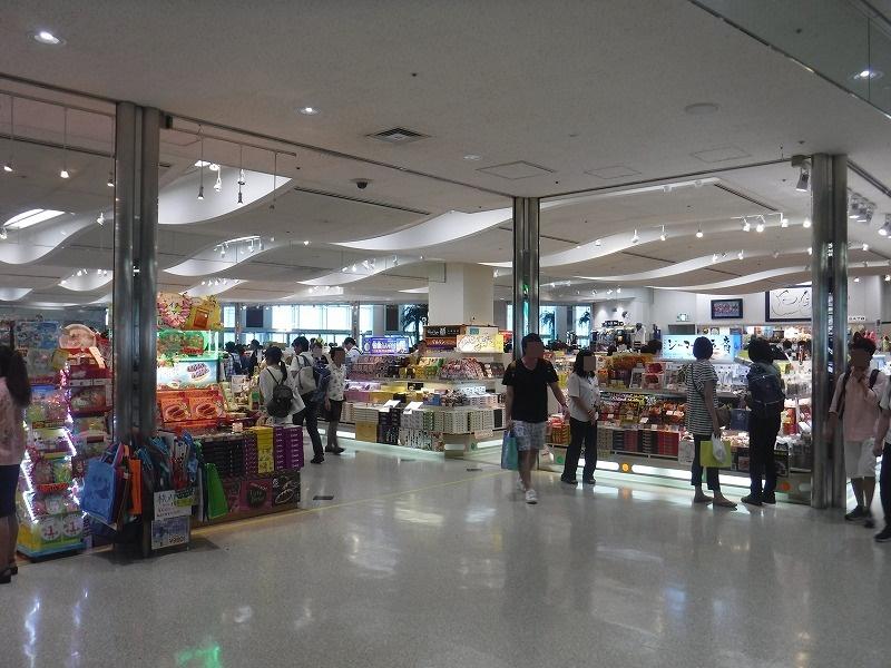 梅雨時期の沖縄空港ロビー売店_観光客の様子