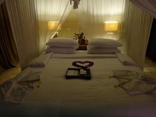 バリ島ウブドのコマネカタンガユダ、ヴァレープールヴィラ夜の照明が灯った室内の天蓋ベッド