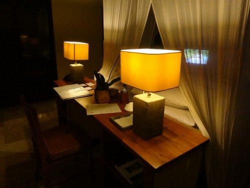 バリ島ウブドのコマネカタンガユダ、ヴァレープールヴィラ夜の照明が灯った室内のベッドサイド