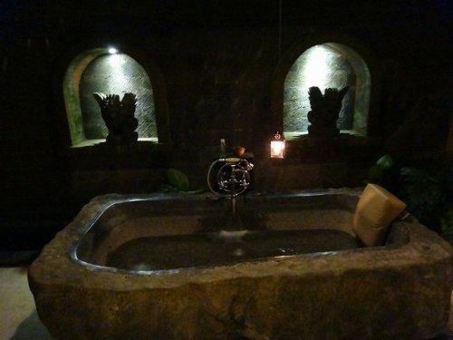 バリ島ウブドのコマネカタンガユダ、ヴァレープールヴィラ夜の照明が灯った室内からみた岩をくり抜いたバスタブ