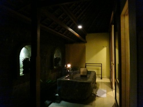バリ島ウブドのコマネカタンガユダ、ヴァレープールヴィラ夜の照明が灯った室内からみた岩をくり抜いたバスタブを外から見た