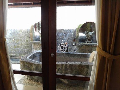 バリ島ウブドのコマネカタンガユダ、ヴァレープールヴィラ室内から岩をくり抜いたバスタブを眺める