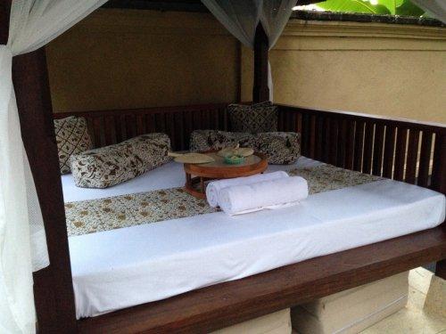 ウブドのプライベートプール付きヴィラ|コマネカアットタンガユダヴァレープールヴィラのプライベートプールにある屋根付きベッドスペースのベッドセッティング