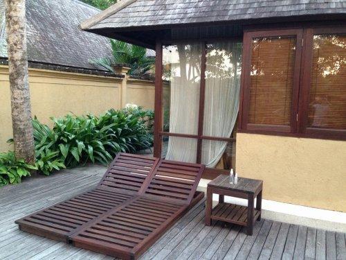 ウブドのプライベートプール付きヴィラ|コマネカアットタンガユダヴァレープールヴィラのプライベートプールの木製ビーチベッドとテーブル